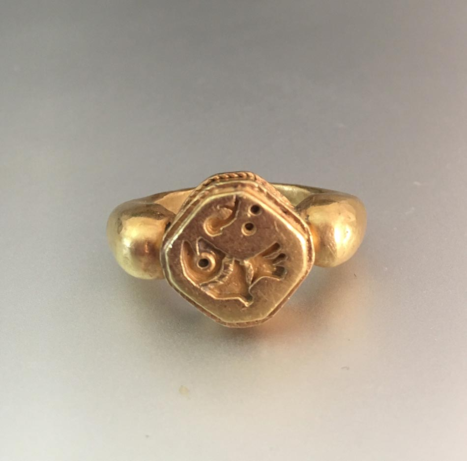 A Gold Ring With Fish Bezel